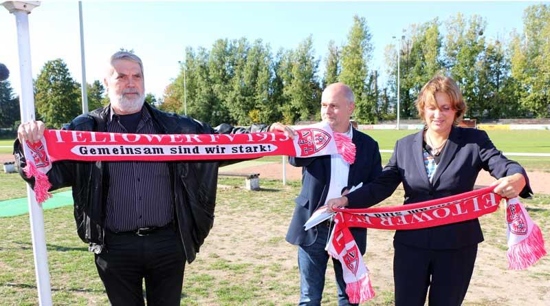 Teltows Bürgermeister Thomas Schmidt nimmt den Zuwendungsbescheid von Ministerin Britta Ernst entgegen. Der Ehrenvorsitzende des Teltower Fußballvereins 1913, Hans-Jürgen Watteroth, übergibt der Ministerin einen Fanschal.
